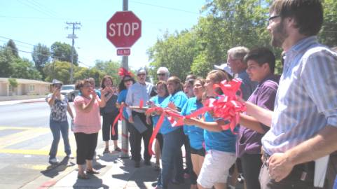 Cutting ribbon to celebrate Detriot Ave Complete Streets project approval.